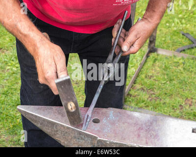 Close up of a blacksmith at work, hammering a piece of red hot iron into shape on an anvil - Stock Photo