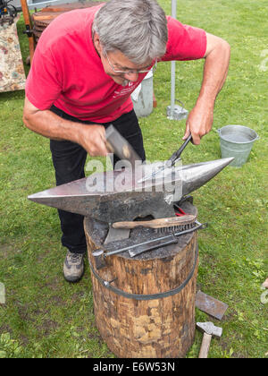 A blacksmith hammering a piece of hot iron into shape on an anvil - Stock Photo