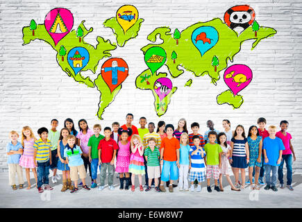 Group of elementary aged children standing in front of a wall of world cartography. - Stock Photo