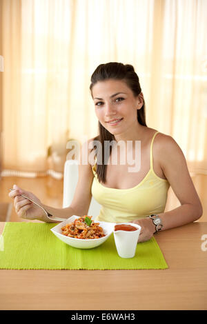 Young happy woman eating italian pasta with tomatoes, parmezan and basil. - Stock Photo