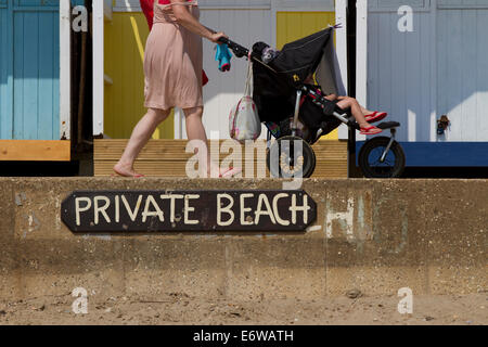 A mother walking her child along Swanage beach. - Stock Photo