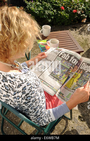 Woman sitting in garden reading the Sun on Sunday red top tabloid newspaper UK - Stock Photo