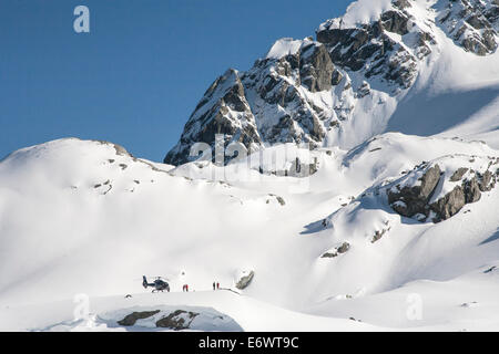 Helicopter landing on the mountain top with winter sportsmen, Heliskiing, South Island, New Zealand - Stock Photo