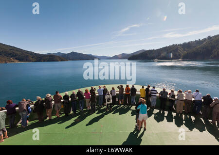 Passengers stand on the bow of the ferry boat entering Marlborough Sounds, Tory Channel, Marlborough, South Island, - Stock Photo