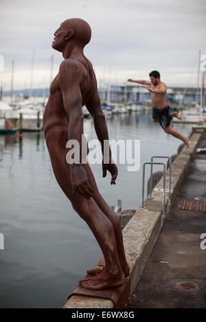 Waterfront with statue Max Patte's Solace of the Wind and swimmer, Wellington, North Island, New Zealand - Stock Photo