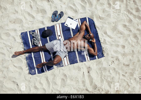 Directly above shot of muscular young African guy sunbathing on beach. Man wearing sunglasses listening to music - Stock Photo