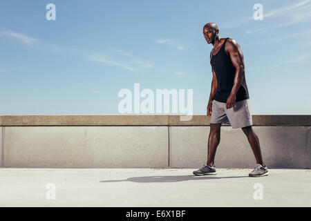 Portrait of young man outdoors ready for his next run. Strong and fit young african male model. - Stock Photo