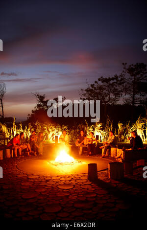 Guests sitting around the camp fire called 'Ring of Fire' in the garden of Hotel Areias do Seixo, Povoa de Penafirme, - Stock Photo