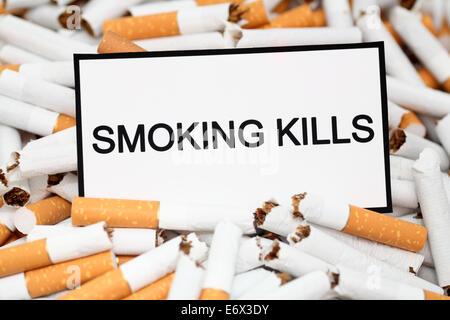 Stop Smoking! Broken cigarettes and warning message 'Smoking Kills'. Close-up. - Stock Photo