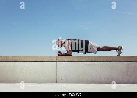 Side view of strong young african athlete doing core exercise on a wall by a walkway. Muscular young athlete exercising - Stock Photo