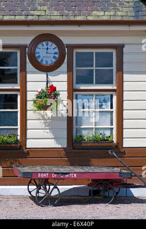 Vintage clock and luggage trolley on platform at Boat of Garten station, Strathspey Steam Railway, near Aviemore, - Stock Photo