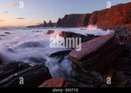 Impressively illuminated red, wild coast of Duncansby Head on the northeastern coast of Scotland with the Duncansby - Stock Photo