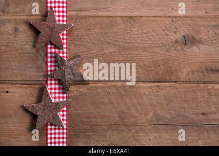 Wooden Christmas stars on checkered ribbon on wooden background for a greeting card - Stock Photo