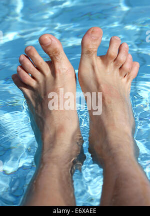 man's feet on the bathtub of a relaxing pool in summer - Stock Photo