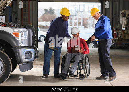 Power plant engineers one with spinal cord injury reviewing work logs in utility garage - Stock Photo