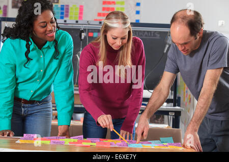 Engineering students reviewing brainstorming notes in lab the man with Aspergers - Stock Photo