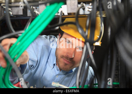 Network engineer bundling cable for structured cabling - Stock Photo
