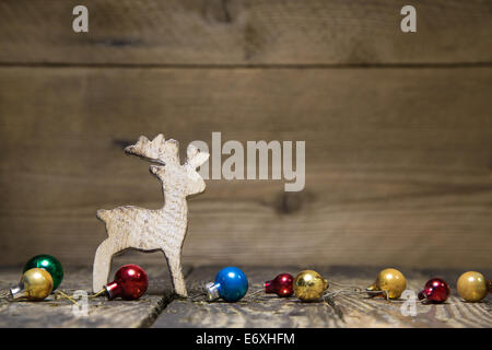 Wooden elk or reindeer on a old rustic country style, background with old christmas balls for a natural greeting - Stock Photo