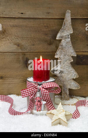 Christmas decoration:wooden tree,stars,candle and snow on wooden background with copy space for a greeting card - Stock Photo