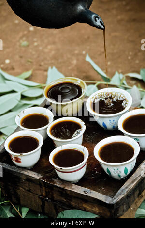 Freshly brewed coffee being poured into cups from a pot, Ethiopia, Africa - Stock Photo