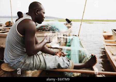 Fisherman repairing fishing nets, Lake Volta, Asuogyaman District, Ghana - Stock Photo