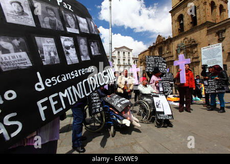 La Paz, Bolivia, 1st September 2014. A Womens Rights activist carries a placard with the photos and names of victims - Stock Photo