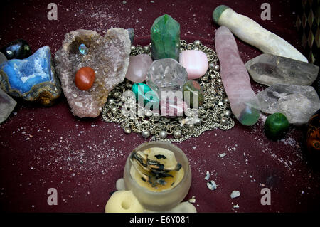 A quartz crystal is surrounded by various polished stones which is in turn encircled with silver chains on alter - Stock Photo
