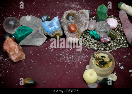 Varied collection of quartz crystals, polished stones, crystal ball and prayer candle on pagan alter. - Stock Photo