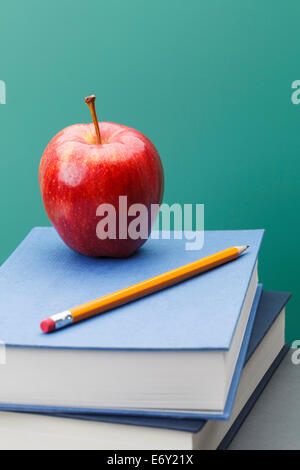 Green Chalkboard, School Books, Sharpened Yellow Pencil and Red Apple in Classroom Setting with Copy Space. - Stock Photo