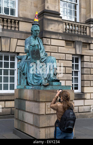 A young woman photographs the statue of David Hume with 'No Parking' cone on his head on the Royal Mile, Edinburgh, - Stock Photo