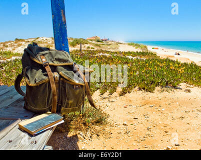 Backpack and book on the porch of a wooden hut next to the shore of a European beach. Backpacking traveller taking - Stock Photo