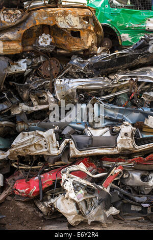A pile of crushed cars in a scrapyard. - Stock Photo