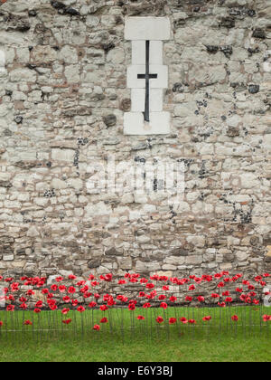 detail of the ceramic poppies exhibit  at the tower of london during heavy rain with the tower wall behind. - Stock Photo