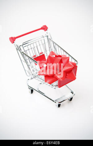 Shopping cart with big red bow on the white background - Stock Photo