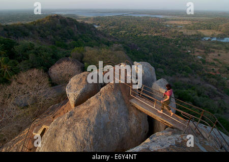 Female tourist walking on top of the Aradhana Gala Rocks on Mihintale mountain, Mihintale near Anuradhapura, Kultur - Stock Photo
