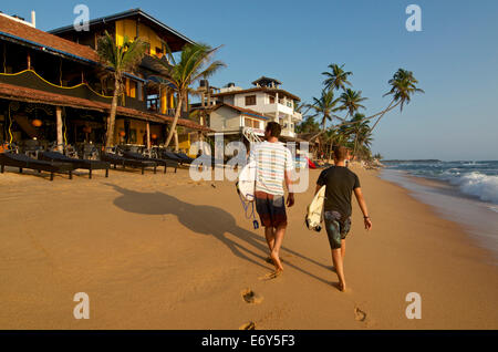 Two male surfers carrying their boards on the beach at Hikkaduwa, Sri Lanka West Coast. South Asia - Stock Photo