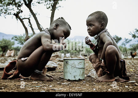 Two children of the Himba tribe eating out of a pot, Kaokoland, Namibia, Africa - Stock Photo