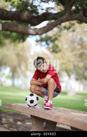 Young boy in the park on a table with football - Stock Photo