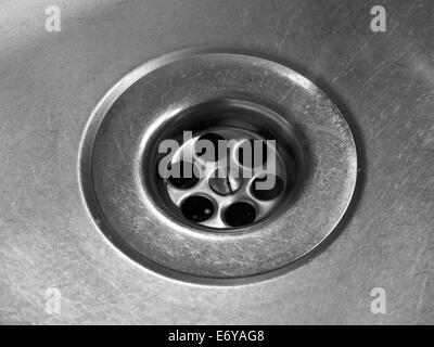 Closeup of drain hole in worn stainless steel kitchen sink - Stock Photo
