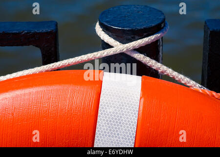 Detail of the orange live saving ring hanging on a black pole against dark water - Stock Photo