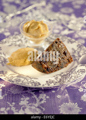 Christmas pudding with brandy butter - Stock Photo