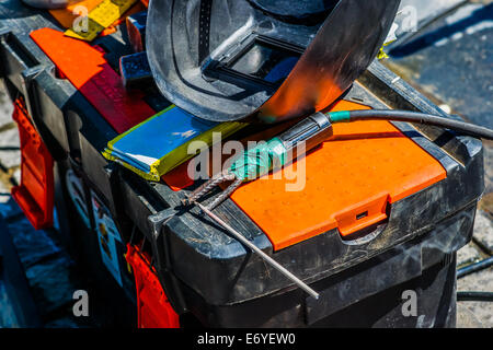 Arc welding accessories and equipment. Closeup view of welding mask, electrodes, and electrode holder on a plastic - Stock Photo