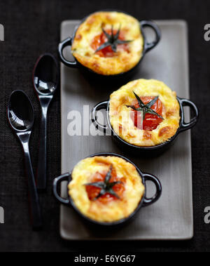 Cherry tomato and goat's cheese savoury puddings - Stock Photo