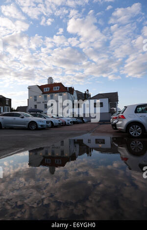 Evening image of the Royal Hotel, on the Seafront at Deal,  Kent. Evening cloudscape is reflected in a large puddle. - Stock Photo