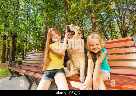 Two girls with happy dog - Stock Photo