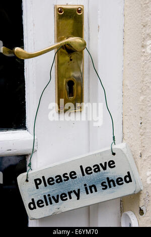 Sign on door handle with the words Please leave delivery in shed - Stock Photo