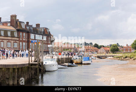 Boats moored in creek in harbour in Blakeney, coastal north Norfolk, UK in summer with cloudy sky - Stock Photo