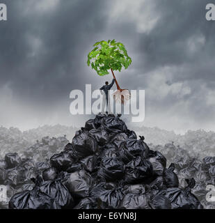 Green businessman concept as a man on top of a mountain heap of garbage holding up a green leaf tree with roots - Stock Photo