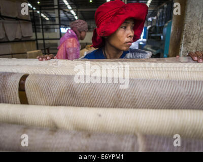 Bo Thong, Thailand. 2nd Sep, 2014. A worker at the Bothong Rubber Fund Cooperative hangs rubber sheets before putting - Stock Photo