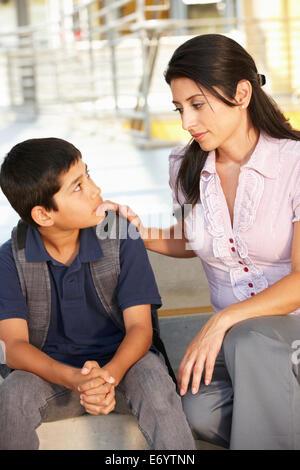 Unhappy Pre teen boy in school - Stock Photo